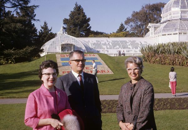 Three well dressed people in front of white-seeming glass greenhouse