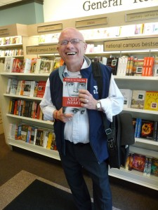 Man in blue vest, standing and holding Cleft Heart in front of bookshelves.