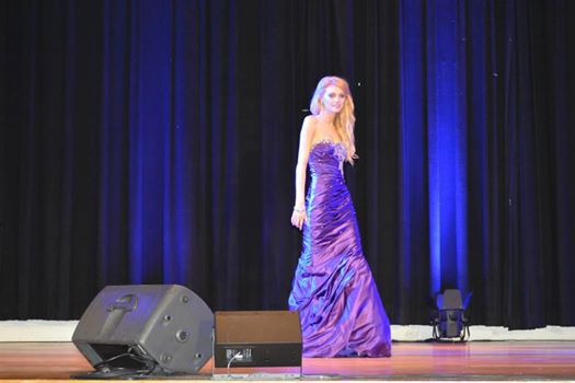 Woman in purple gown crossing the national stage.