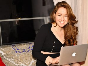 Woman with bronze laptop computer on lap.