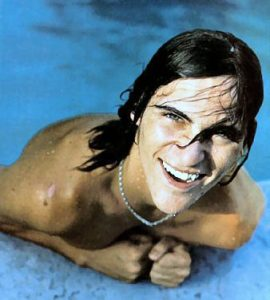 J Phoenix in water, smiling with cleft lip affected teeth.